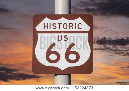 Historic US Route 66 highway sign with sunset sky.