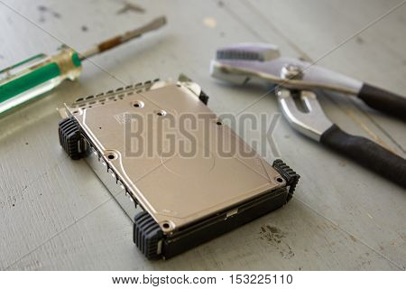 Broken and Destroyed Hard Drive Disk and Tools on Wooden Table.