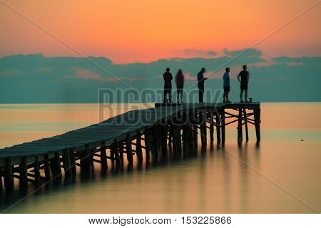 people greeted the sunrise on a wooden quay