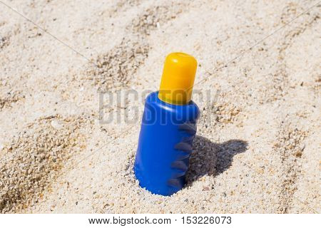Sun oil cream on the sand at beach