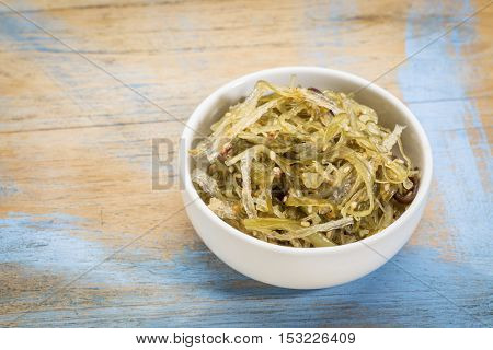 a small ceramic bowl of seaweed salad based on agar-agar against grunge wood
