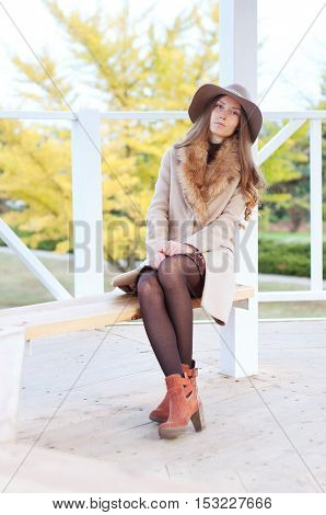 Elegant caucasian redhead woman with freckles and green eyes in fedora hat and beige coat with fur resting on the bench. City street fashion.