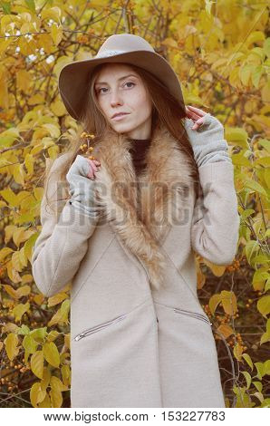Retro look. Beautiful ash blond with freckles long hair in fur collar coat and fedora hat outdoors in autumn