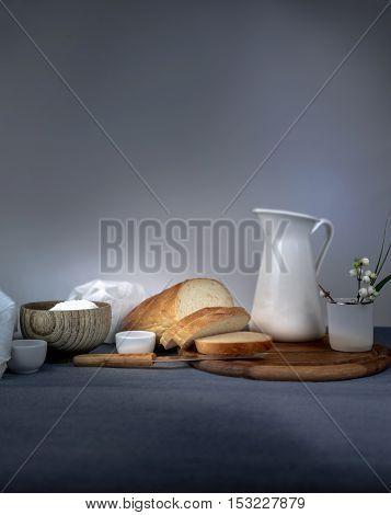 continental breakfast, dairy, jug, bread on a wooden board