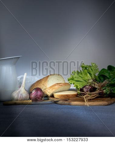 still life. jug, bun, onion, garlic spinach on a blue tablecloth