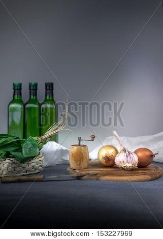 still life. jug, bun, onion, garlic, spinach on a blue tablecloth space for text