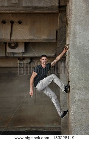 Men T-shirt parkour in urban space. He climbs the wall. Sport in the city. Movement is life.