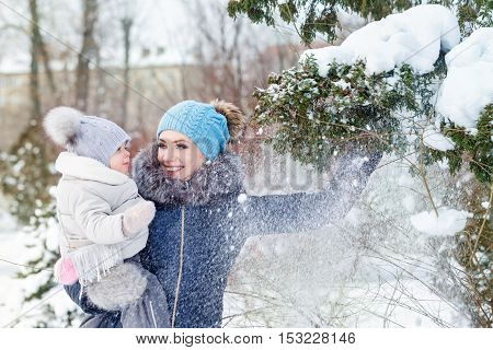Mother and young daughter embracing in a winter park. Mother and daughter with snow shot down trees. Happy family. Childhood and parenthood happiness. Close portrait.