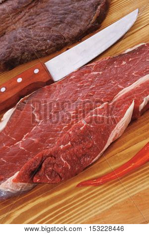 grilled and raw beef steak fillet meat with knife on wooden board isolated over white background