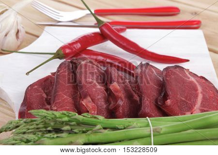 fresh beef meat slices asparagus spices cutlery wooden table pepper hot chili vegetables served garlic light cutting board ready to cook