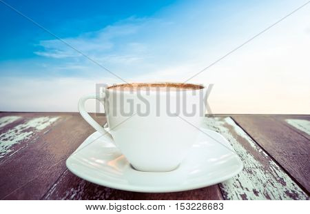 Hot coffee on old wood table with sky background - soft focus