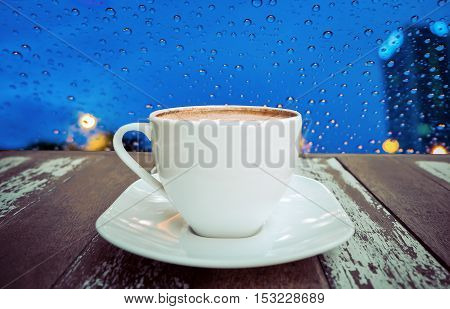 Hot coffee on old wood table with raindrops on window background - soft focus