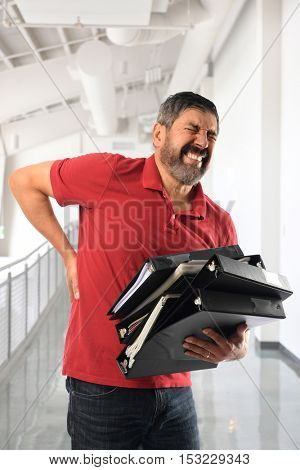 Hispanic businessman experiencing back pain while carrying binders