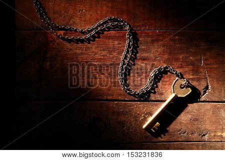 Door key with chain on old wooden background under beam of light