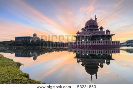 View and reflection of Putrajaya Mosque with stunning clouds and sky during sunrise