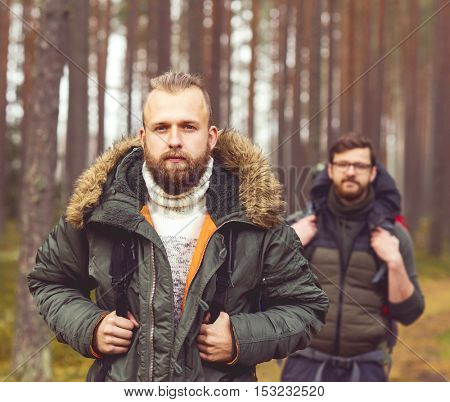 Camp, adventure, traveling and friendship concept. Man with a backpack and beard and his friend hiking in forest. Autumn color and hipster filter.