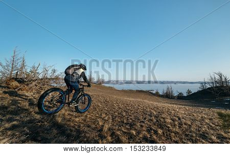 Fatbike also called fat bike or fat-tire bike - Cycling on large wheels. Traveller athlete cyclist rides with mountains in the background scenic view.