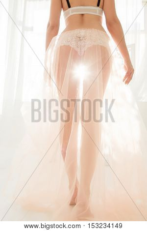 Beautiful nude woman silhouette. Female legs making step to light in white diaphanous fabric