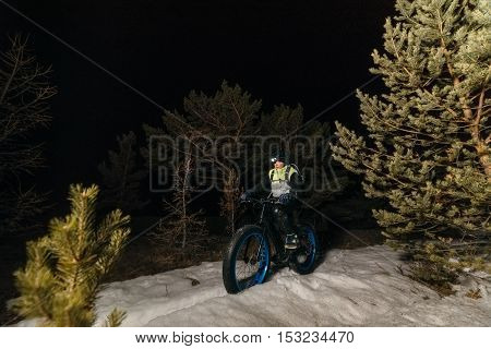 Fatbike also called fat bike or fat-tire bike - Cycling on large wheels. Traveller athlete cyclist rides at night in the snow in the woods with a flashlight on his head.