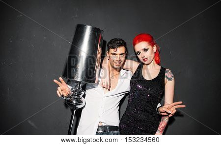 Happy man in white shirt posing for photo with informal girl on gray background. Redhead woman photographing with stranger at party.