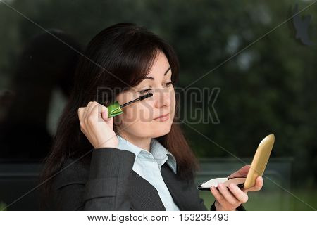 middle-aged woman in business suit puts make-up on her eyes