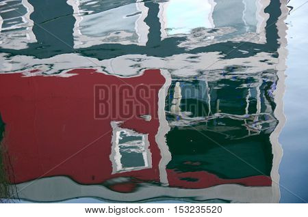 A red and grey boathouse is reflected in the calm waters of Victoria's Inner Harbour British Columbia