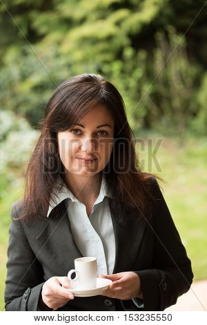 middle-aged woman in business suit drinks cup of coffee