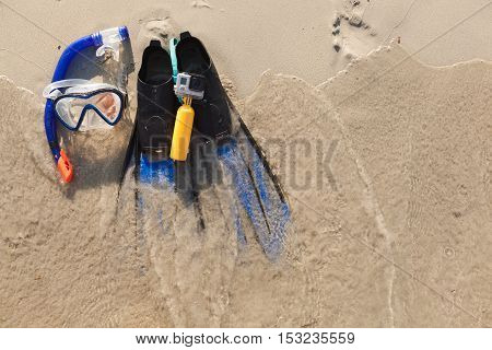 blue mask, flippers and camera lying on sand