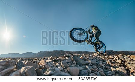 Fatbike also called fat bike or fat-tire bike - Cycling on large wheels. Traveller athlete jumps on the bike on the rocky shore of Lake Baikal, with mountain views.