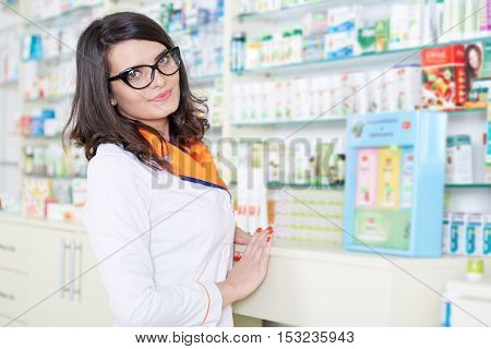 Closeup of female pharmacist over blurred background of medicine