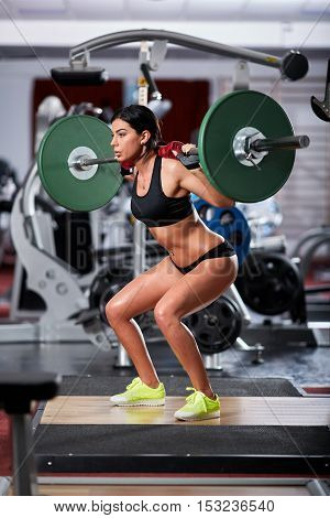 Young woman doing squats with barbell in the gym
