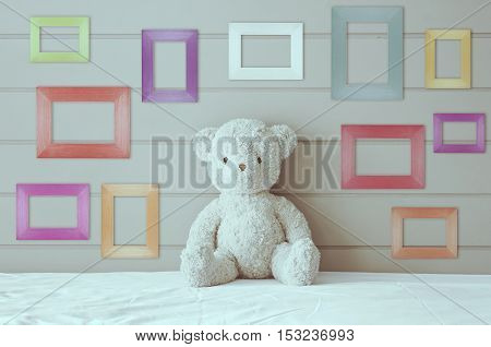 vintage teddy bear sit on the white bed with blank multi-color or fancy picture frame at the headboard and brown wall background for gift and surprise
