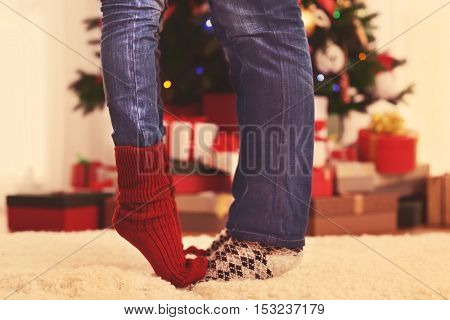 Legs of couple on fur carpet in room with Christmas tree and present boxes