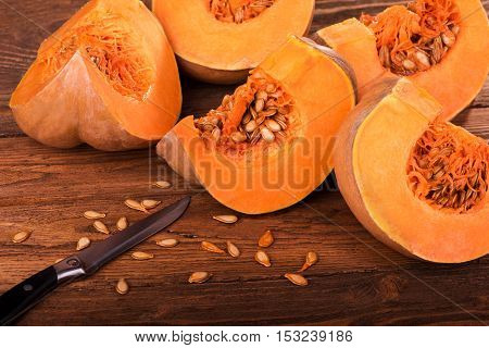 Pumpkin with seeds cut into pieces on a wooden table. Healthy eating