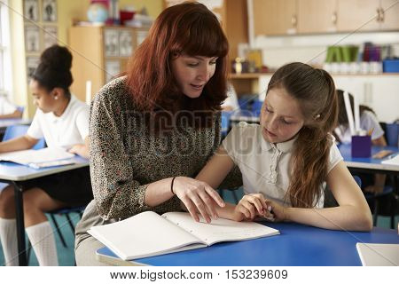 Teacher helps a girl at her desk, close up both looking down