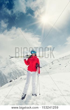 Beautiful young woman with ski in high mountains during sunny day.