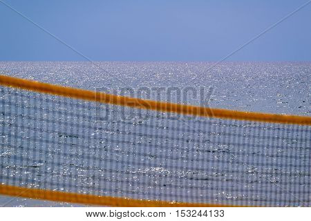 indistinct grid of beach volleyball closeup against the background of the sea and horizon