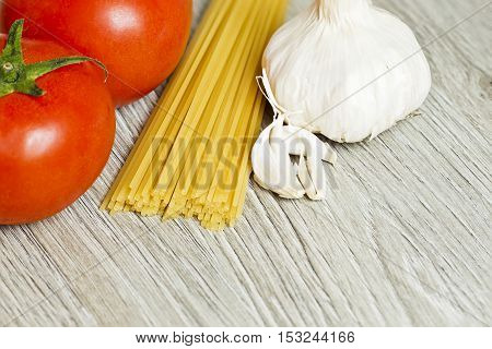Fresh raw tomatoesgarlicand spaghetti ready for a meal on a textured wooden board