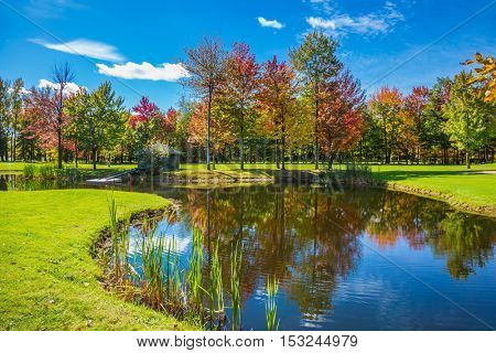 Very nice park. Golf Club on the road to Bromont, French Canada. Concept of Golf tourism. Red, orange and green autumn foliage is reflected to clear water of the lake