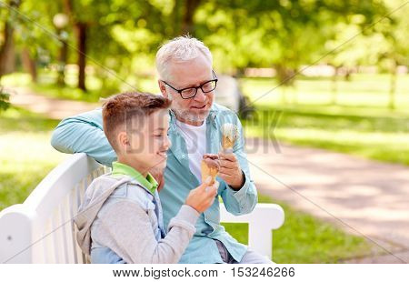 family, generation, communication and people concept - happy grandfather and grandson eating ice cream at summer park