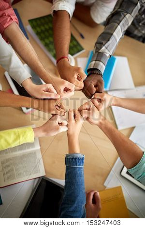 education, school, success, teamwork and people concept - group of international students making fist bump over table