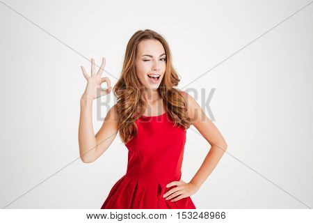 Portrait of a pretty brunette woman in red santa claus dress showing okay sign and winking over white background