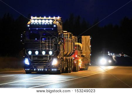 SALO FINLAND - OCTOBER 21 2016: Blue Volvo FH16 Kung Fu Panda show truck of KMS Palvelu Oy with bright lighting accessories drives along highway in darkness.