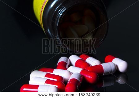 Red and pink antibiotic capsule on bottle in black background