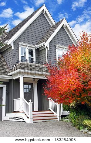 Beautiful upscale house in canada with a Maple leaf tree next to the front door.