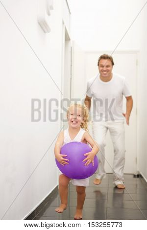 Full length portrait of cute little girl holding balloon and running with her father in back at home