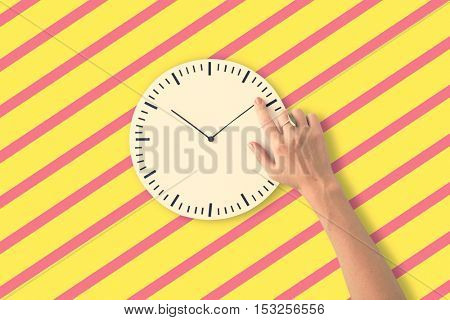 hand adjusting the time on clock
