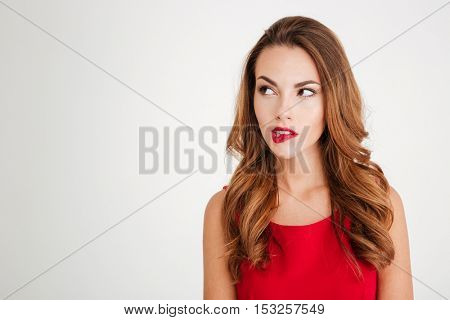 Unsure pretty young woman in red dress looking away isolated on a white background