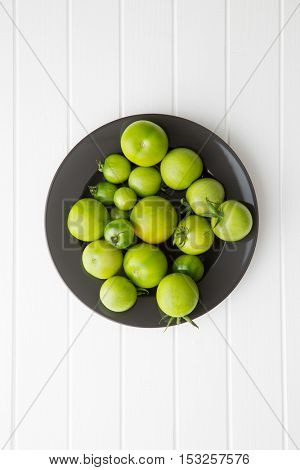 Unripe green tomatoes on kitchen table. Top view.