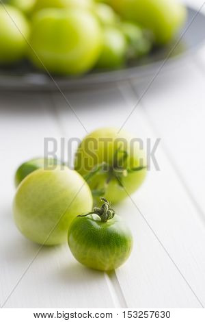Unripe green tomatoes on kitchen table.
